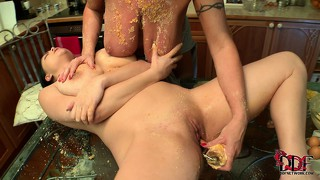 Two lesbian babes packing massive tits get messy in the kitchen
