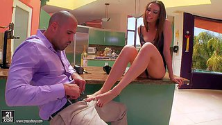 Arousing long haired young brunette beauty tiffany tyler with long legs and tight ass in black dress gives arousing footjob to her boyfriend and gets banged hard from behind in the kitchen