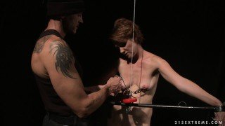 Slave is bound and gagged as her breasts get tortured in a dungeon