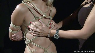 Naked tied up slave blonde chary with natural tits, clean pussy and hot ass gets punished in the dark of the dungeon by clothed dark haired mistress mandy bright. domina spanks blonde's ass with desire.