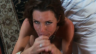 The brunette's sweet face looks up at you while sucking your giant cock very well