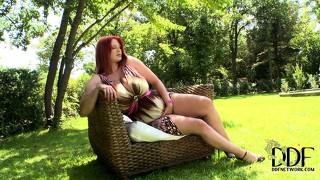 In the garden, a sexy redhead shows off her huge boobs and her marvelous ass