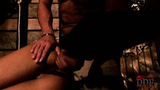 Tanned brunette bound in a dungeon gets her ass dildoed deep