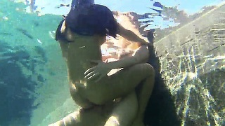 Young and hot lasses swim in the pool and kiss each other gently