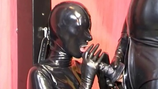 A kinky couple dressed in latex gimp suits having oral sex fun