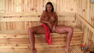 Buxom brunette alone in a sauna poses and rubs, tasting her juices