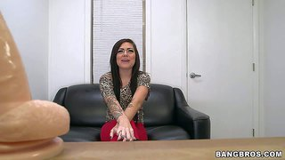 Innocent looking long haired slim brunette babe with large arm tattoo and provocative glasses takes off red tights and boots and reveals her nice shaped natural boobs at the interview