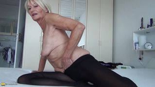 Horny mature masturbates on the bed