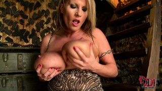 In the barracks, a gorgeous blonde milf reveals her huge tits and her shaved cunt