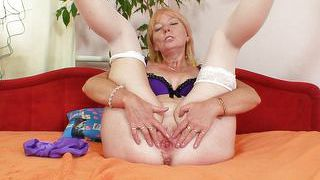 Mature blonde spreads her legs to show her wide pussy