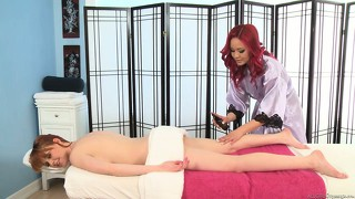 Redhead masseuse rubs down a brunette and she gives some pussy rubbing
