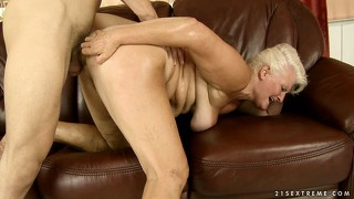 Old blonde gets her sagging tits covered in cum by a young stud