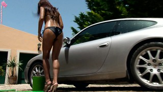 Slender witch is washing car and slowly undressing in front of cameras