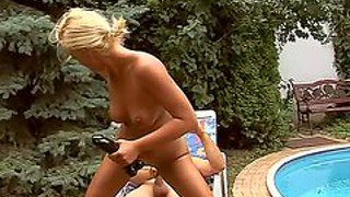 Young horny blonde with natural boobs stuff her hairless twat with huge black dildo while her hubby is fucking her in the ass in awesome outdoor action by the pool