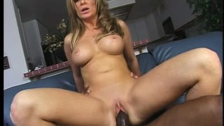The busty blonde mom bounces on his black rod before he drills her peach doggy style