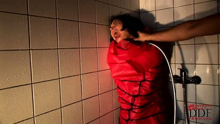 Sexy slave in full body bondage gets fucked with a shower head