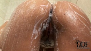 Sexy brunette gets all lathered up in the shower and rubs her slit