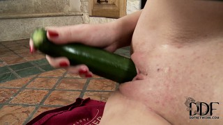 In the kitchen, the sexy babe with adorable tits drills her holes with a courgette
