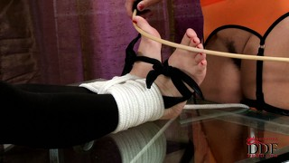Slave gets tied by her mistress, and her feet and clothespins them