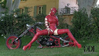 Latex lucy is a kinky adult model. masked lady poses in her red rubber outfit in the garden. she shows off her nice ass and touches her pink shaved pussy for you viewing pleasure.