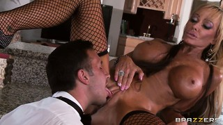 Bronzed blonde skank in fishnets rides a cock in the kitchen