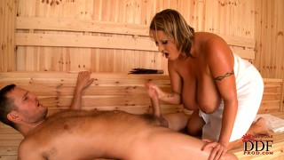 In the sauna, a stacked tanned milf sucks a big cock before it invades her pussy